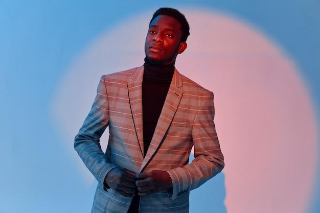 スーツ自信ネオンの背景にアフリカ人探しの男。高品質の写真