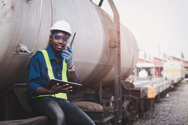 태블릿을 사용하여 기차를 수리하기 위해 헬멧, 숲, 안전 조끼를 입은 아프리카 기계 엔지니어