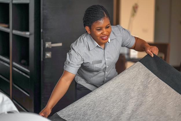 ホテルの部屋でベッドを作るアフリカのメイド。スタッフメイドメイキングベッド。ベッドを作るアフリカの家政婦。