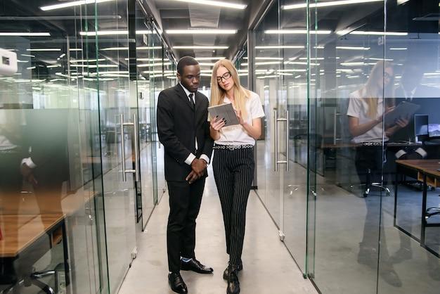 タブレットpcが空のオフィスの廊下に立って、新しいプロジェクトについて話しているアフリカの男性と白人の女性会社員。