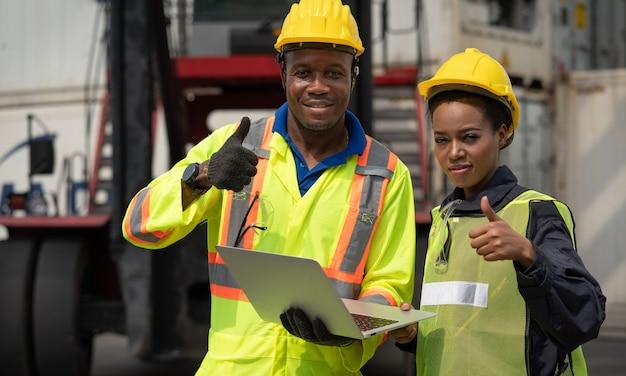 アフリカの男性と女性の労働者は、倉庫のコンテナ貨物船で働いているラップトップで親指を表示します