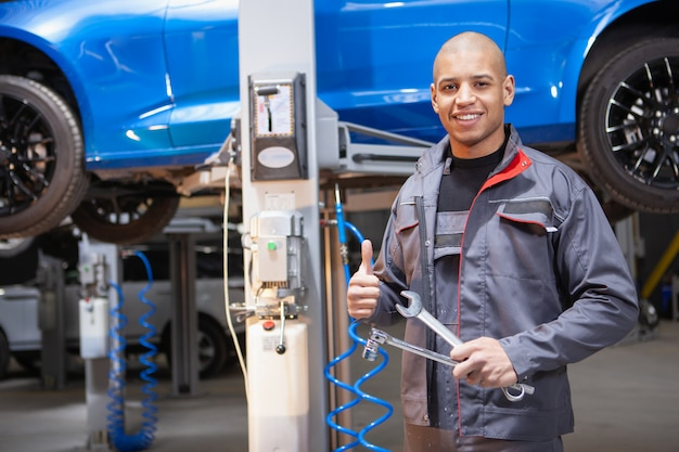 African male car service worker repairing cars at his workshop