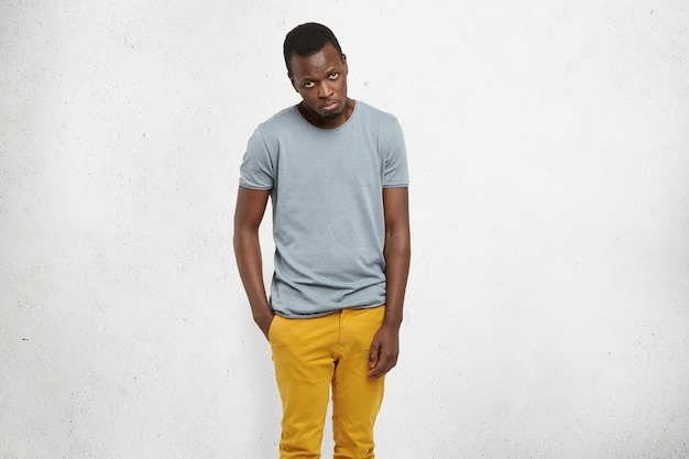 African male in casual t-shirt and mustard pants, looking at camera with guilty expression