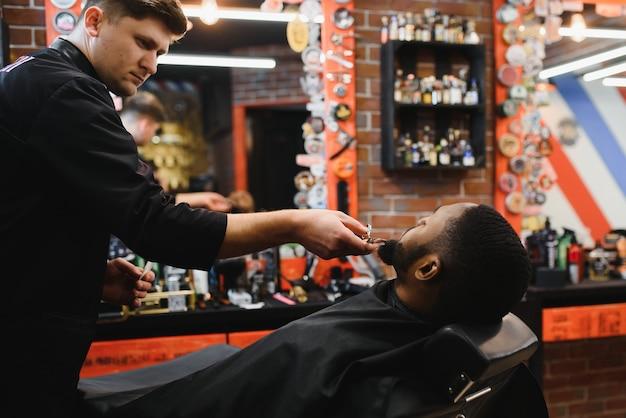 Африканский клиент-мужчина стригется в парикмахерской от профессионального парикмахера