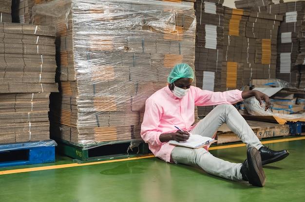 음료 가공 공장의 창고에 쌓인 판지 상자 패키지의 순서를 확인하고 살균 유니폼을 입은 아프리카 남성 재고 관리 관리자