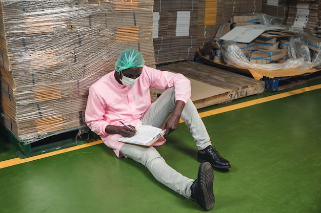 African male inventory control manager in sterile uniform sitting and checking order of cardboard box package stacked in warehouse at beverage processing plant
