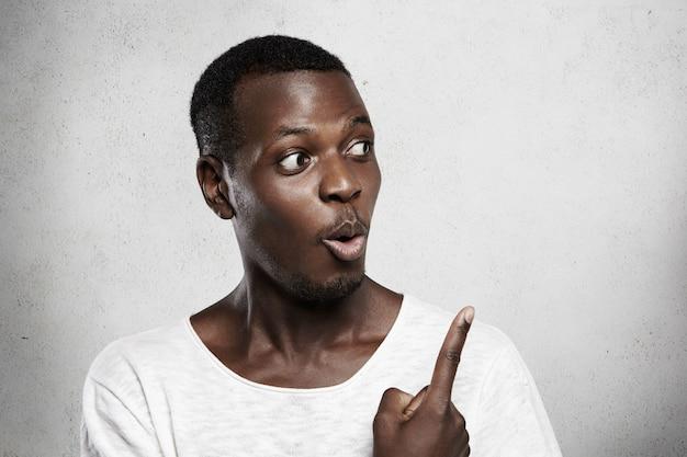 空白の壁にショックを受けた表情で探している白いtシャツのアフリカの男性モデル。広告コンテンツのコピースペースで指を指します。