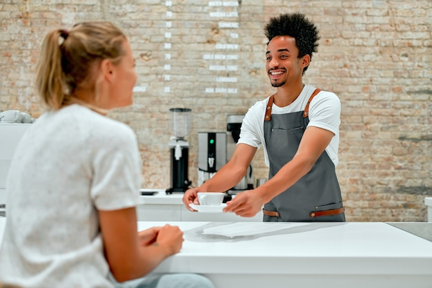 African male professional barista in apron serves a cup of coffee to a client and smiles.