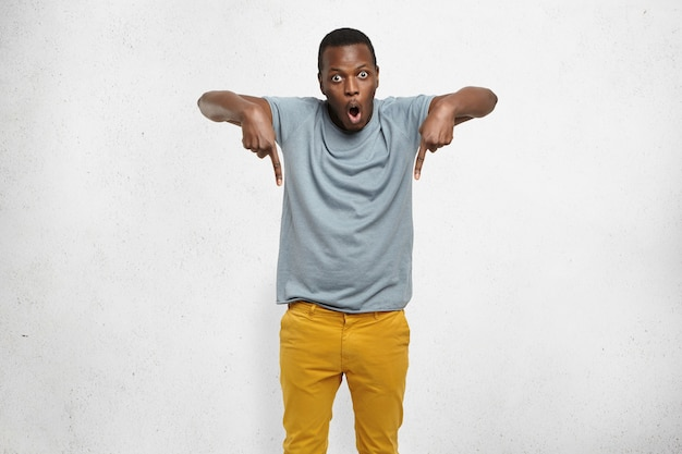 African male in t-shirt and mustard pants pointing fingers down having surprised look