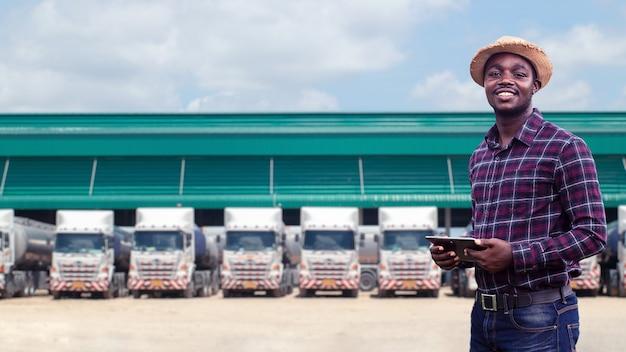 Африканский водитель грузовика мужского пола держит планшет и проверяет маршрут для нового пункта назначения. на заднем плане припаркованные грузовики. концепция транспортного обслуживания.