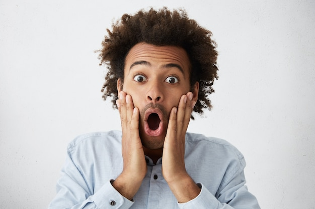 African male with funky hairstyle screaming, opening mouth wide opened and touching face