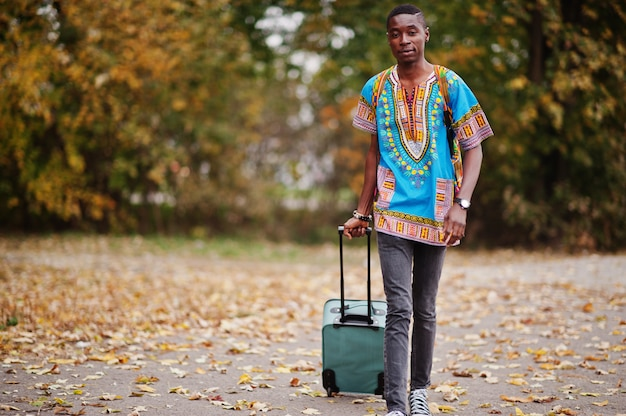 African man in africa traditional shirt on autumn park with backpack and suitcase. emigrant traveler.