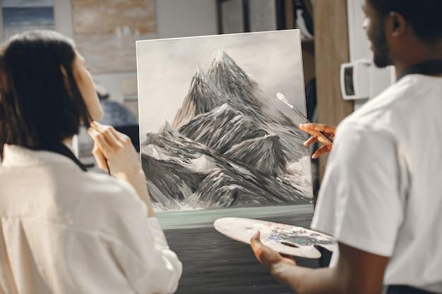 Африканский мужчина и женщина в классе живописи рисуют на мольберте.