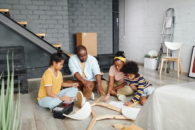 アフリカ人の男性と彼の妻は、息子と娘の間でそれを組み立てる方法について相談しながら、木製の椅子の部品の1つを指しています