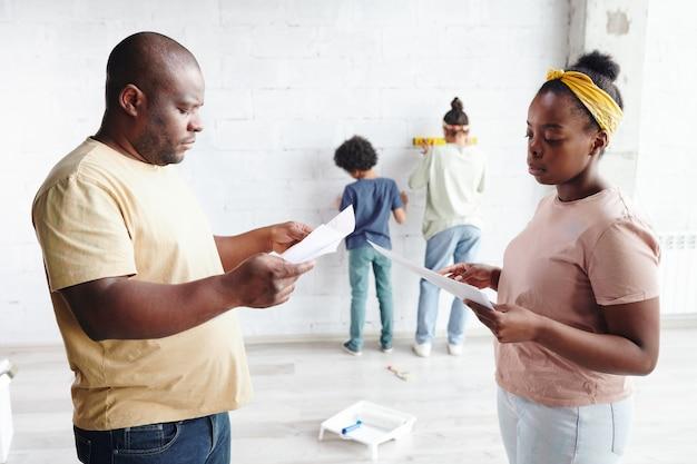 2人の子供が壁で遊んでいる間、家具の組み立て手順で紙を議論するカジュアルウェアのアフリカの男性と女性