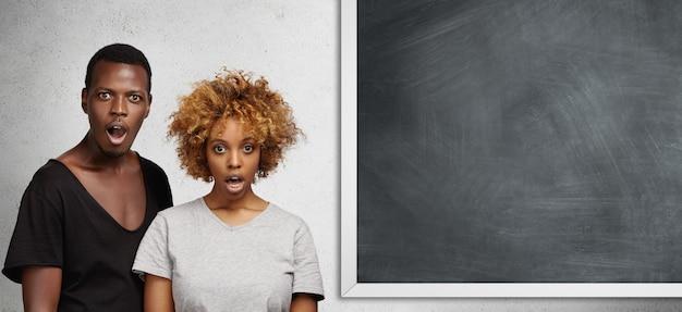 Африканский мужчина и женщина, стоящие рядом друг с другом у пустой доски с местом для текста или рекламного контента, выглядят удивленными и шокированными, широко открывая рты в полном недоверии