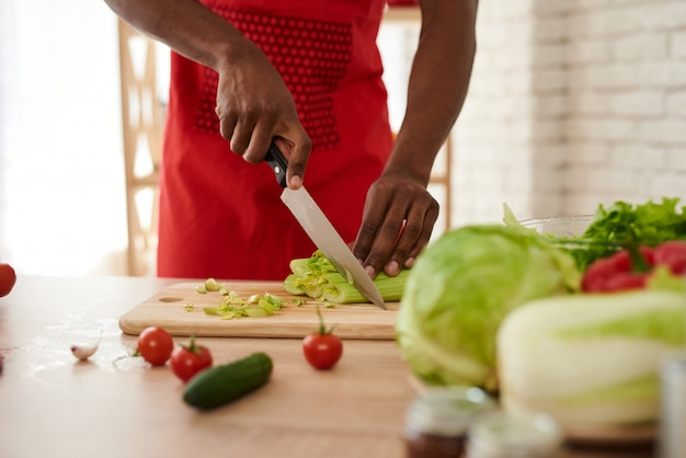 African man in apron sliced celery in kitchen.