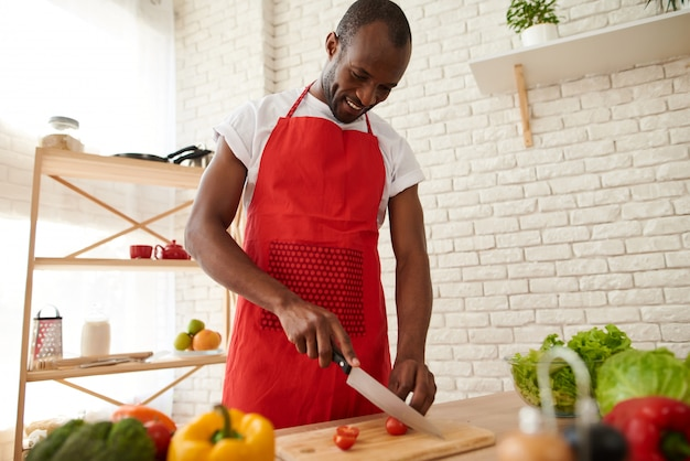 African man in apron slices tomatoes in kitchen.