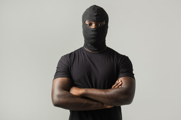 African man in a black mask and a black t-shirt on a gray wall