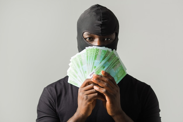 African man in a black robber mask, and in a black t-shirt on a gray wall with euro in hands