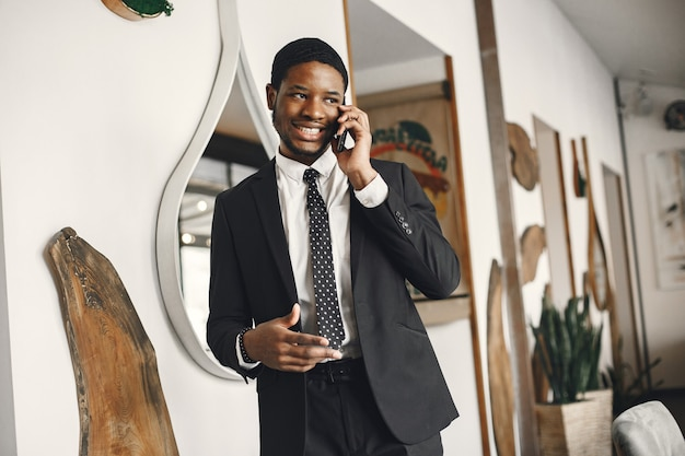 African man in a black suit talking on a mobile phone.
