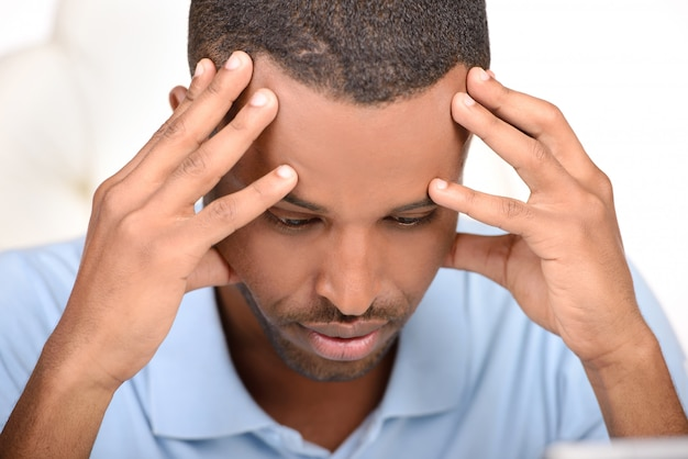 African man in blue shirt touching forehead with hand.