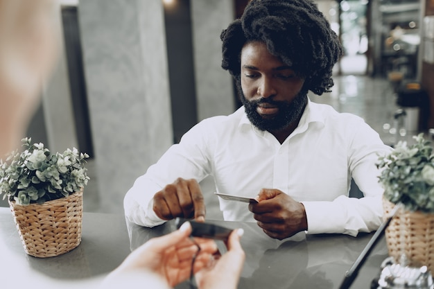 African man businessman paying for the stay in hotel with credit card
