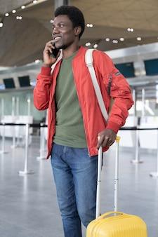 Африканский мужчина вызывает такси в аэропорту