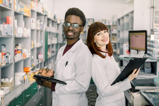 African man and caucasian woman pharmacists are posing near table with cashbow in apothecary.