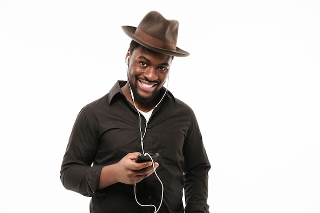 African man chatting by phone and listening music