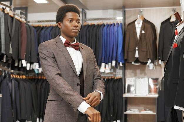 Африканский человек, выбирая элегантный костюм в модном бутике.