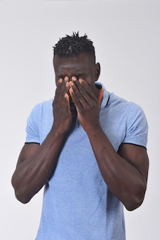 African man cover his face with his hand