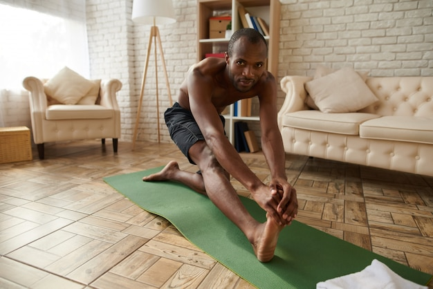 African man does stretching exercises on floor.