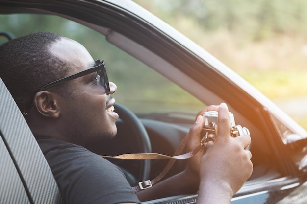 African man driver holding a film camera and smiling while sitting in a car with open front window.