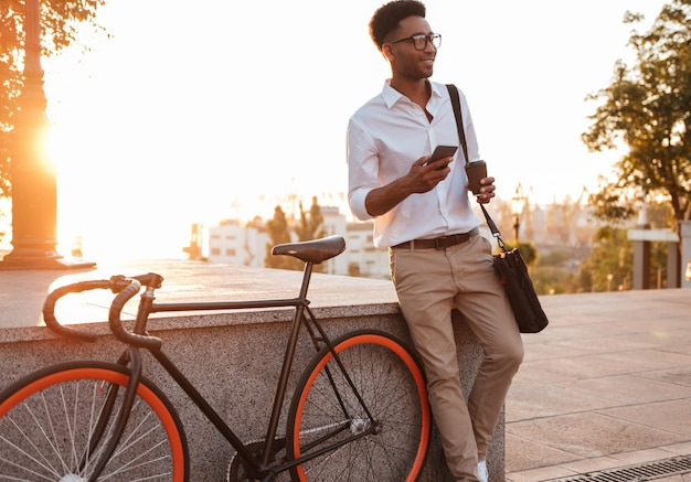 African man in early morning standing near bicycle