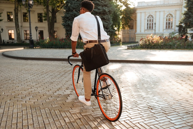 African man early morning with bicycle walking outdoors