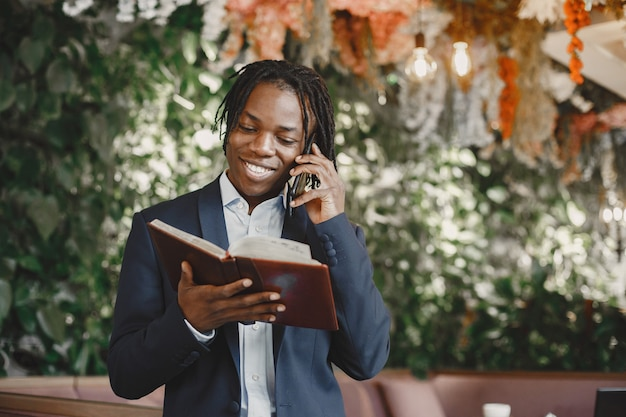Uomo africano. ragazzo in abito nero. maschio con un telefono cellulare.