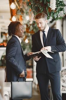 Uomo africano. ragazzo in abito nero. le persone miste lavorano insieme.