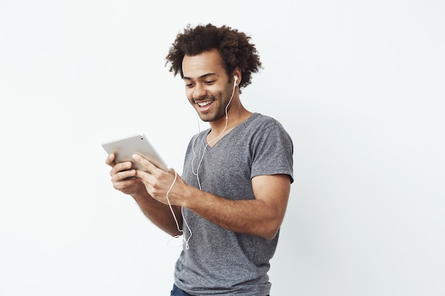 African man in headphones laughing holding tablet talking or watching and enjoying a comedy show or browsing