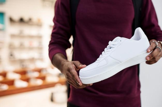 白いスニーカーを持っているアフリカ男