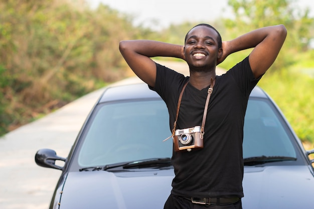 African man holding a film camera and smiling  with a car.