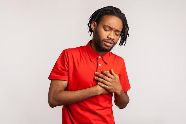 胸に手をつないで、心臓にひどい急性の痛みを感じ、心臓発作のリスクがあるアフリカ人男性。