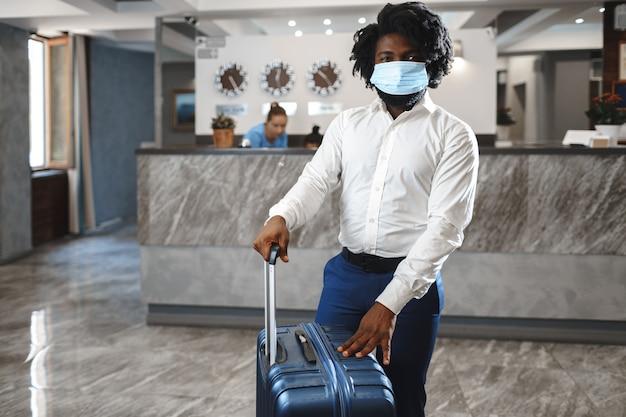 コロナウイルスから保護するために防護マスクを身に着けているスーツケースを持つアフリカ人のホテルのゲスト