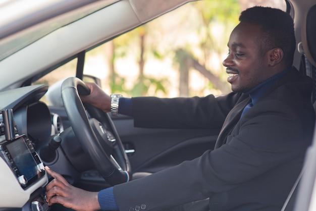 Африканский мужчина в черном костюме сидит за рулем с улыбкой и счастливым