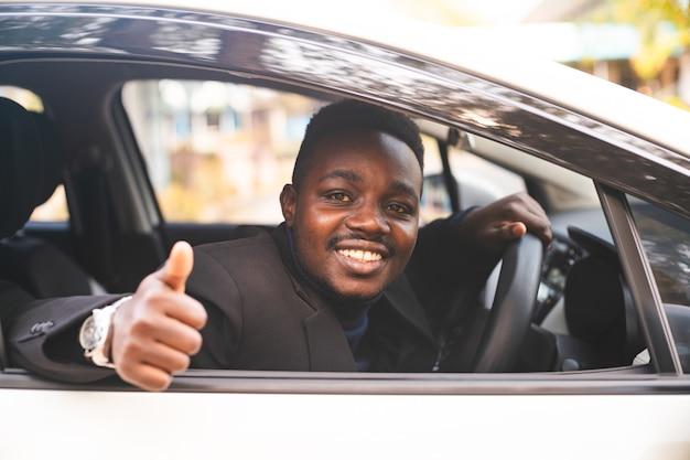 미소와 행복으로 바퀴 뒤에 앉아 검은 양복에 아프리카 남자