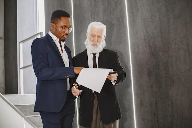 Африканский мужчина в черном костюме.