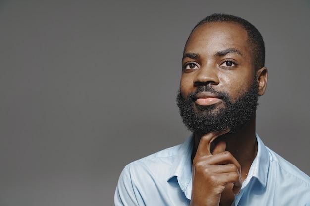 スタジオでアフリカ人。白い壁。青いシャツを着た男。