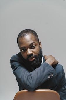 スタジオでアフリカ人。白い壁。スーツを着た男。