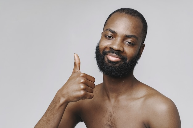 Африканский мужчина в студии. белая стена. человек без одежды.