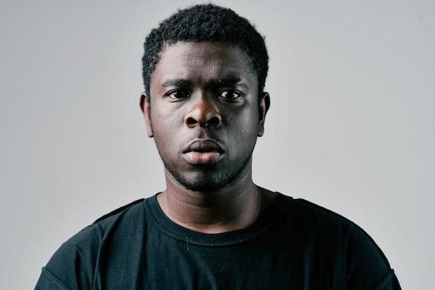 クローズアップポーズの黒のtシャツファッションスタジオでアフリカの男